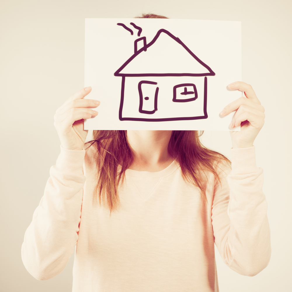 a woman holds up a piece of paper in front of her head with a house drawn on it