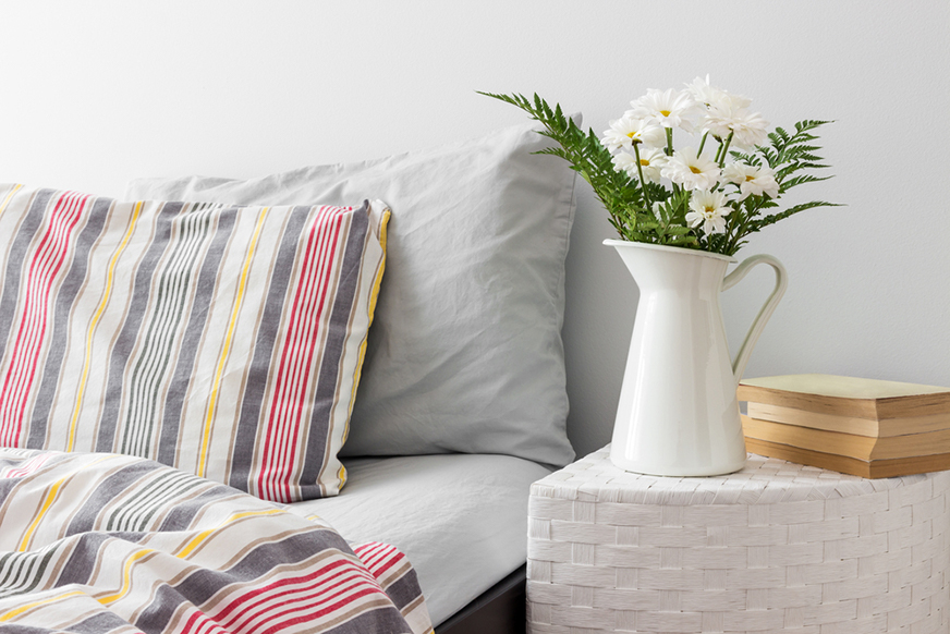 a bed and nightstand with a vase of flowers