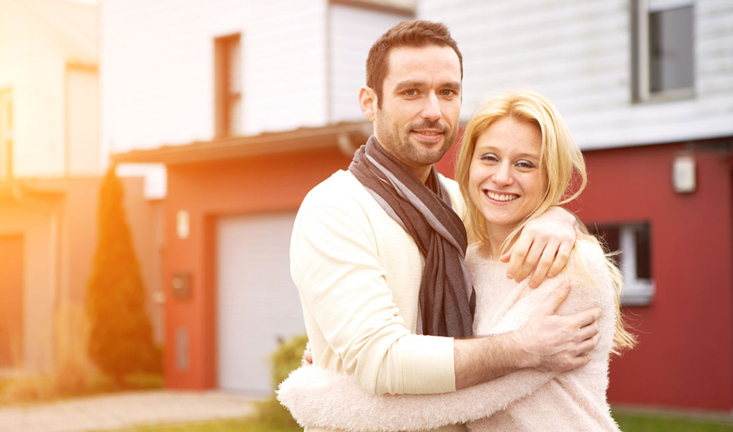 a couple embraces in front of their home