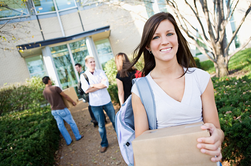 College-aged girl carrying box in front of apartment building
