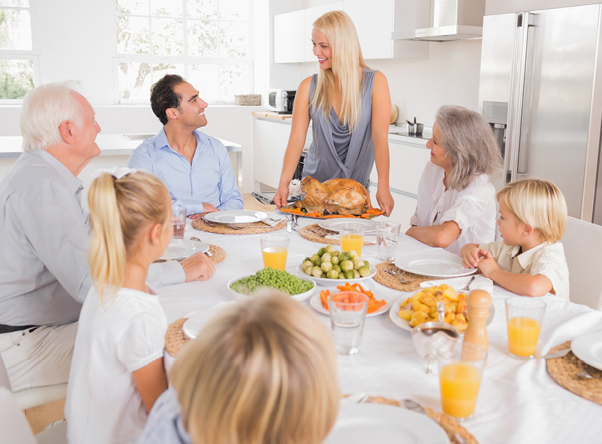 a family eating thanksgiving dinner sitting around a dining table