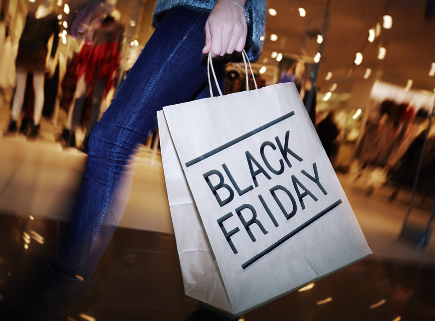"""a woman holds a shopping bag at the mall that reads: """"black Friday"""""""