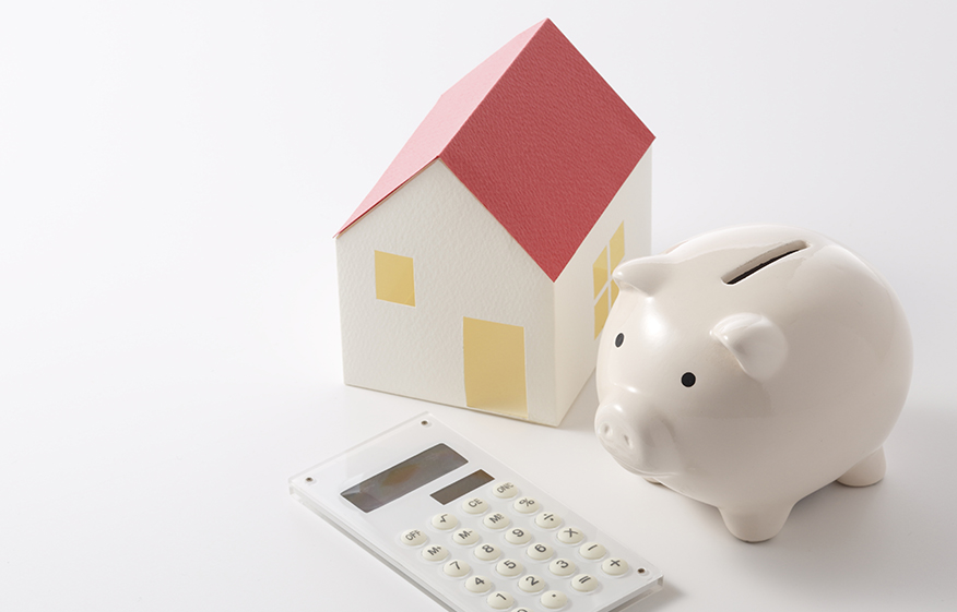 a piggy bank next to a model house and calculator