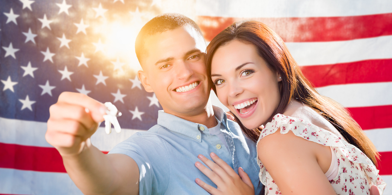 a couple holding keys to new house in front of an American flag
