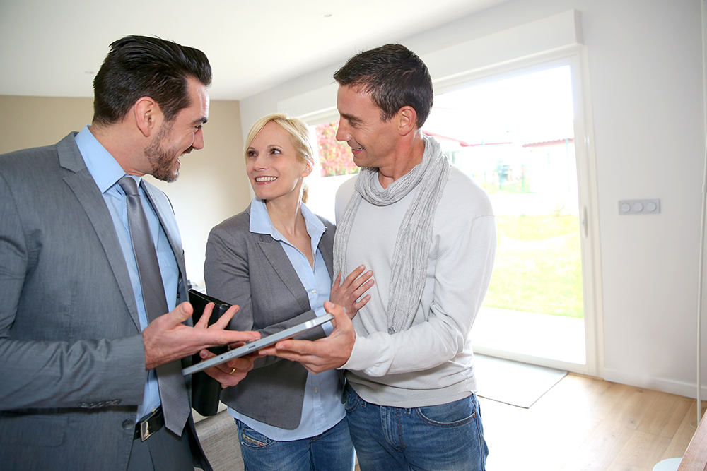 a couple checking out a house with a realtor
