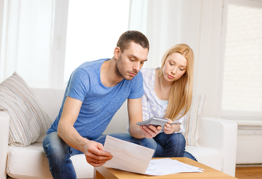 a young couple sits on a couch looking at documents and holding a calculator