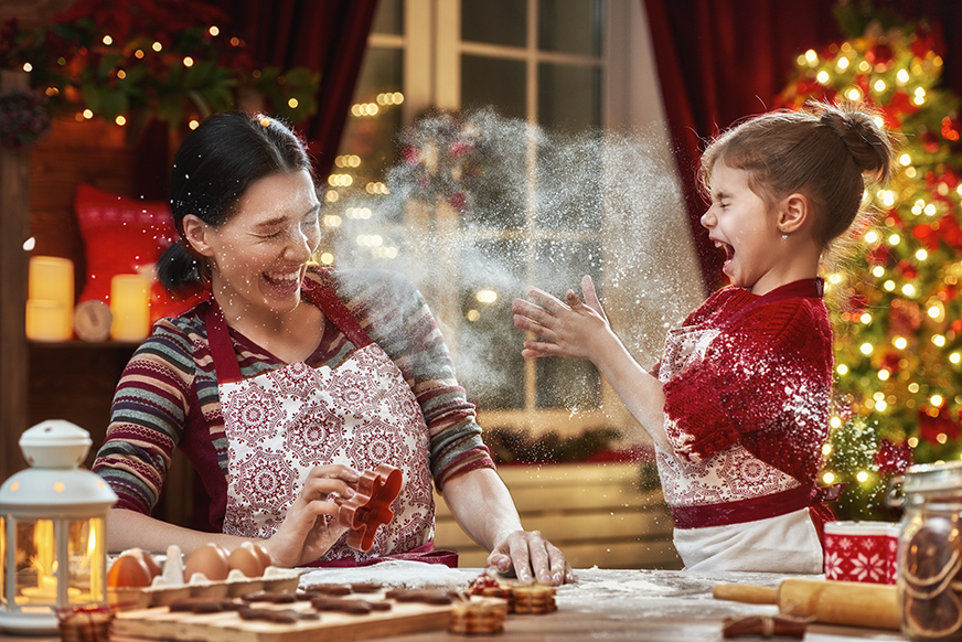 a mother and daughter are baking cookies at christmas and flour is flying in the air