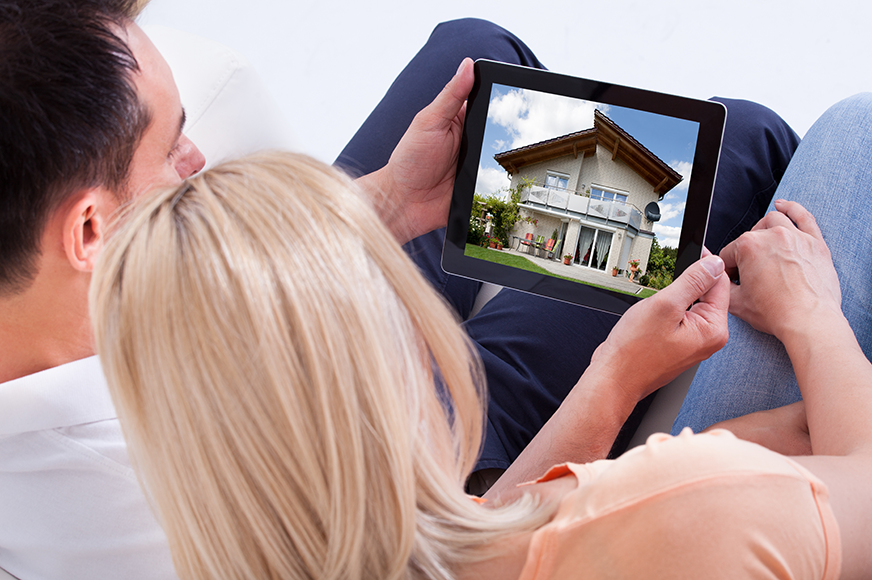 Couple looking at homes on tablet