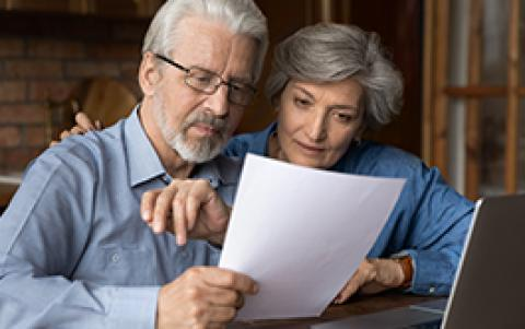 middle aged couple looks at paperwork
