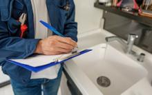 Home inspector looking a sink and writing on a clipboard