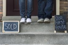 "Two people standing on a porch with chalk signs that read ""sold"" and ""our new home"""